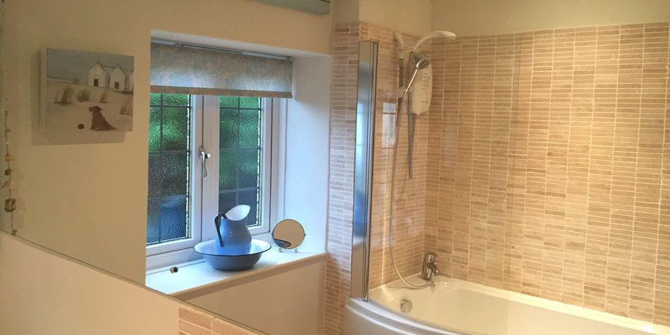 Stylish bathroom equipped with bath and shower, at Greenwich cottage, Chideock, Dorset.