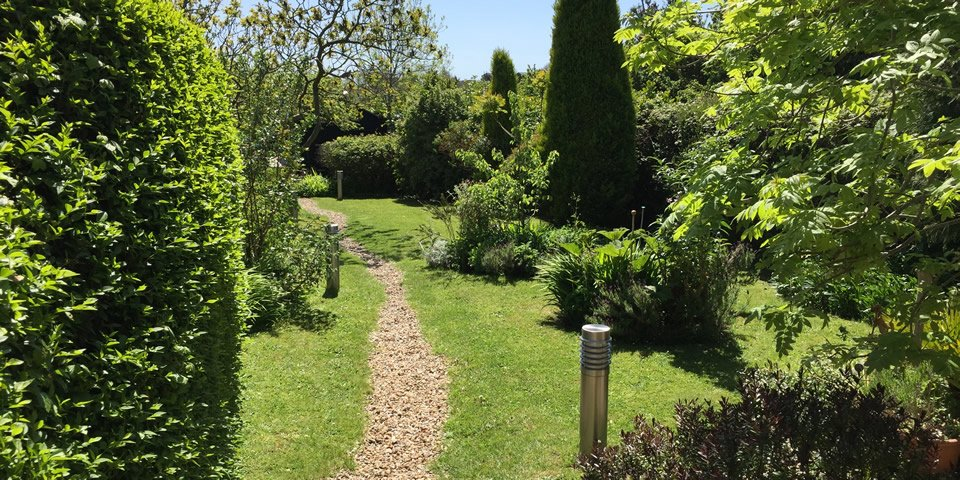 Greenwich Cottage Garden. Greenwich cottage features a large garden lined with trees and shrubs, a decked area equipped with garden furniture and lighting, and stunning views of the National Trust Golden Cap Estate and the World Heritage Jurassic Coast.